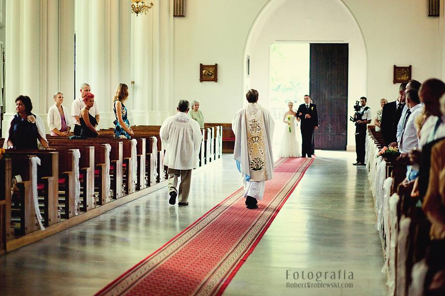 Kapłan podąża w stronę młodych. Fotograf Pruszkow czeka na posterunku.
